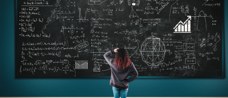 student in front of blackboard showing maths problems