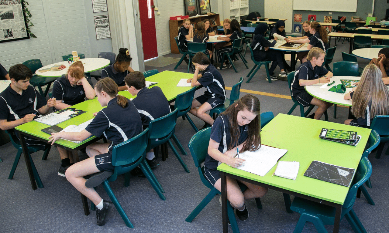 image of a classroom with students seated in groups around desks