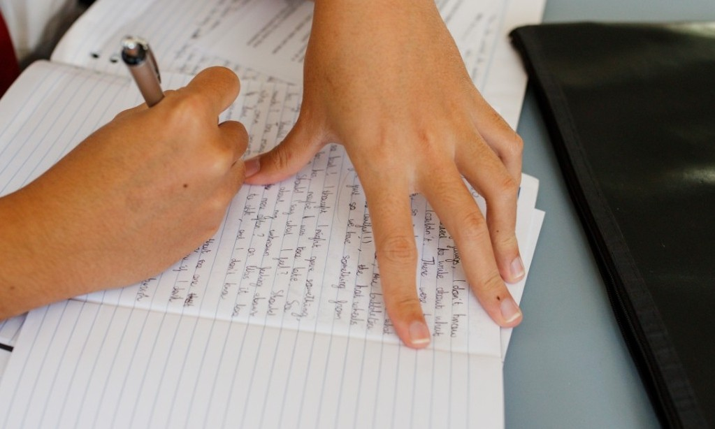 close up of a hand holding pen above a page of writing in a workbook