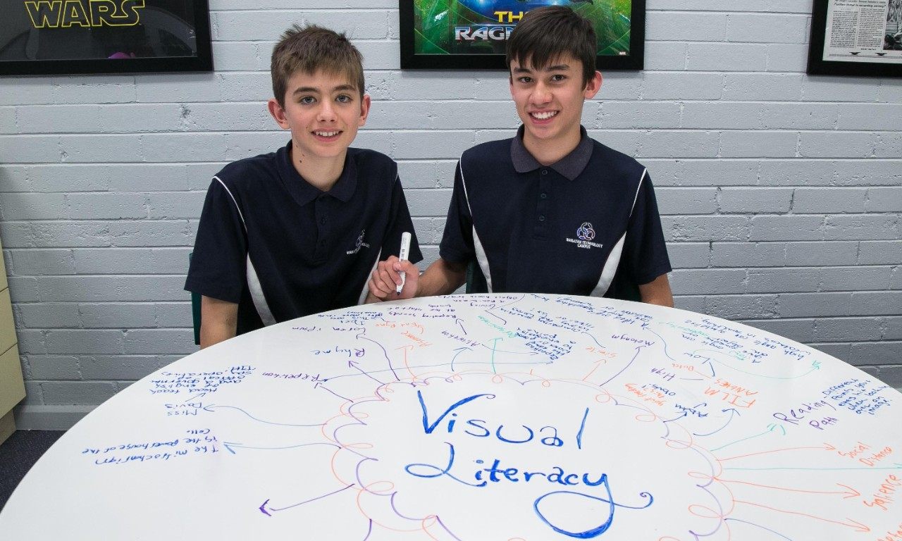 Two student sitting at a white desk with a digital literacy mindmap written on it in whiteboard marker