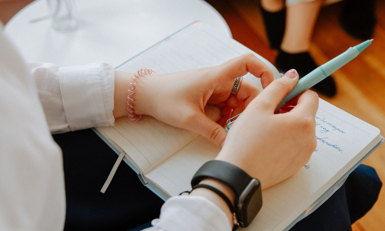Close up of a woman's hands holding a pen and resting on a notepad on her lap