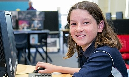 High school student sitting in front of desk top computer and looking towards the camera